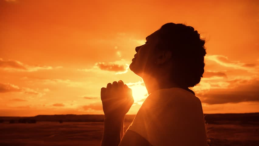 the girl prays. Girl folded her hands in prayer silhouette lifestyle at sunset. slow motion video. Girl folded her hands in prayer pray to God. girl praying asks forgiveness for sins of repentance