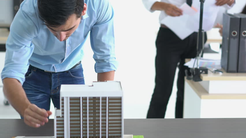 Architects are working on a building model at modern office. Designer are developing architecture. concept of construction, development and creative idea.