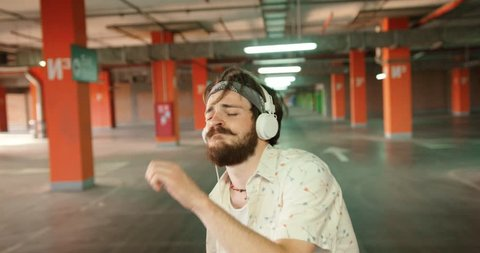 Joyful positive hipster man with dark beard and bandana actively dancing while listening to music on the earphones. 4k. Parking lot location.