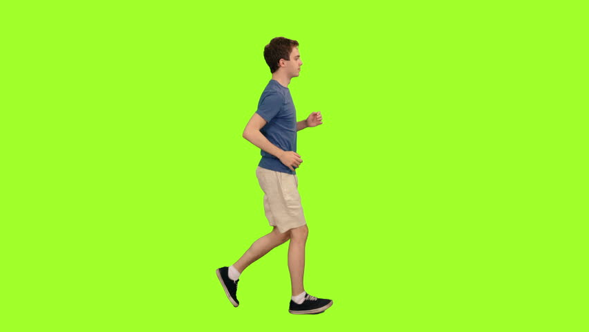 Young caucasian man in shorts and blue t-shirt jogging on green chroma key background, Side view, 4k pre-keyed footage