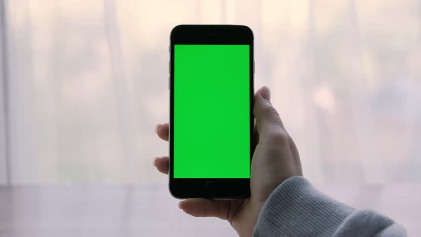 Close-up of a woman's hands holding a smartphone with green screen. | Shutterstock HD Video #1014596171