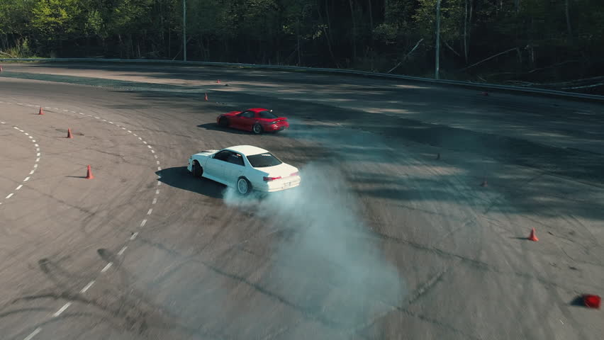 Drifting cars shot from above with drone. Drone chasing drifting car at race track.