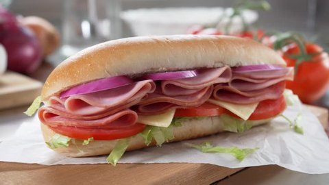 A delicious submarine hoagie sandwich with deli meat, lettuce, tomato, onion and cheese.