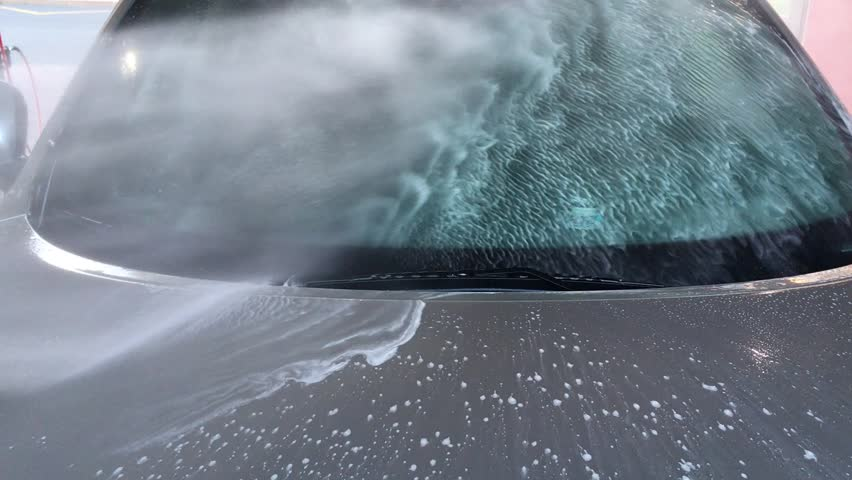 The video shows a contactless car wash, powerful water pressure with foam on the glass and hood, flows down, clean | Shutterstock HD Video #1014626771