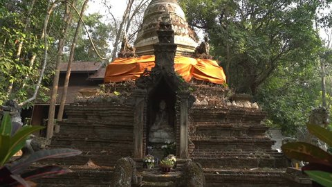 Dolly shot of ancient pagoda at Wat Pha Lat temple in forest