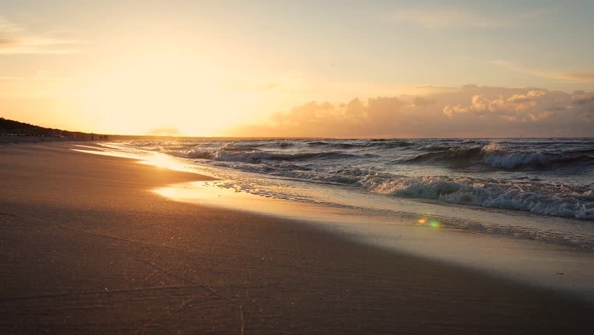 Beautiful sunset on the beach reflected on wet sand with incoming ocean waves in slow motion. Fast moving camera.   Shutterstock HD Video #1014659891