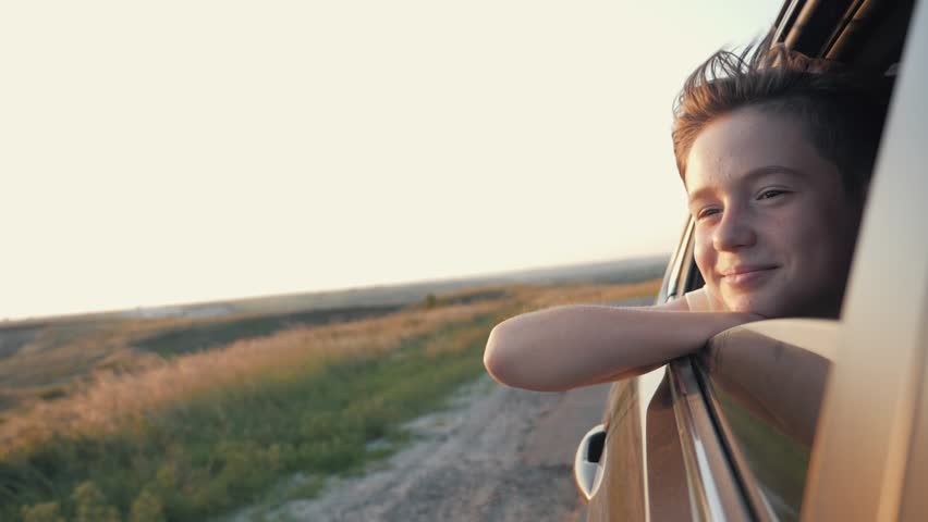 Teen boy looking out the car window. Summer trip with family | Shutterstock HD Video #1014677951