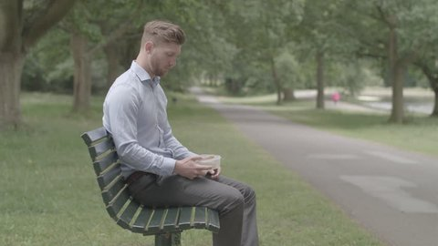Man Sitting On Bench Eatc Lunch and Experiences Heartburn Pain - Ungraded