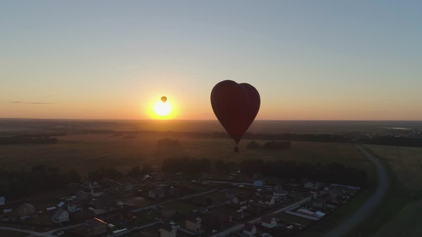 Aerial view Hot air balloon shape heart in sky over field in countryside, beautiful sky and sunset. Aerostat fly over countryside.
