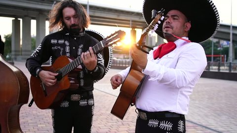 Trio of Mexican musicians mariachi give street concert in the city. Live camera. Slow motion