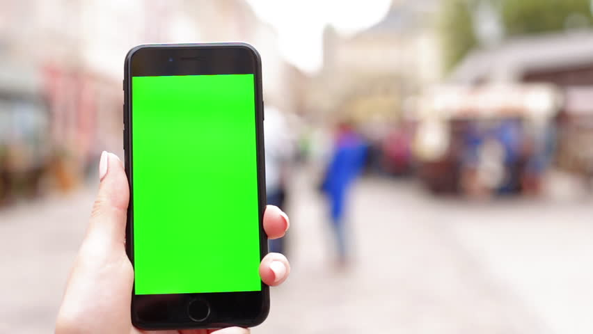 Female hand holding vertical black smartphone with green screen chroma key for tracking motion on the blurred city street background in sunny day. Close-up shot filmed in 1080p HD | Shutterstock HD Video #1014791561
