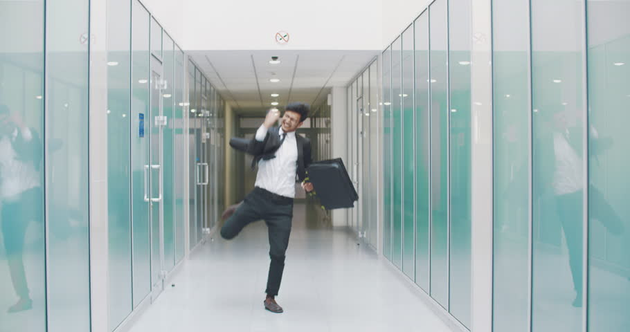 Young turkish businessman walking down the office hall, talking on phone, then celebrating successful business deal. business, victory concept 4k | Shutterstock HD Video #1014792521