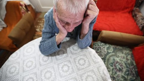 SLOW MOTION: Sad elderly man sitting alone at home. Older gentleman expressing sadness, with head buried in his hands.