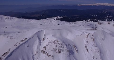 Aerial drone video zoom out backwards camera movement of rocky north face couloirs in snow and cornice on top with ski center reveal
