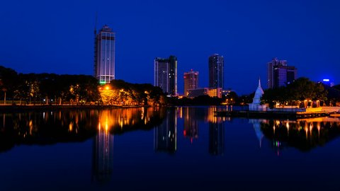 Sri Lanka. View of Beira Lake in Colombo, Sri Lanka with buddhist temple and illuminated modern buildings at sunrise. Night to day time-lapse. Clear sky