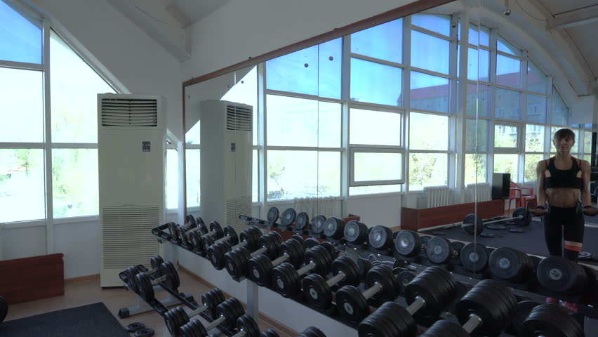 Athletic young woman doing bicep curls with dumbbells at gym and looking at her reflection in the mirror. #1014805211