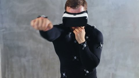 side view of sport athletic man in VR goggles and motion-capture suit with sensors boxing in slow motion training in virtual reality cyberspace fighting battle concentrated face sportsman beating