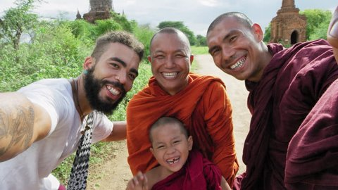 Authentic real monks and African American man tourist traveler in Bagan Mayanmar / Burma doing selfie picture or video with  smartphone, ancient pagoda view of Bagan.  Slow motion.