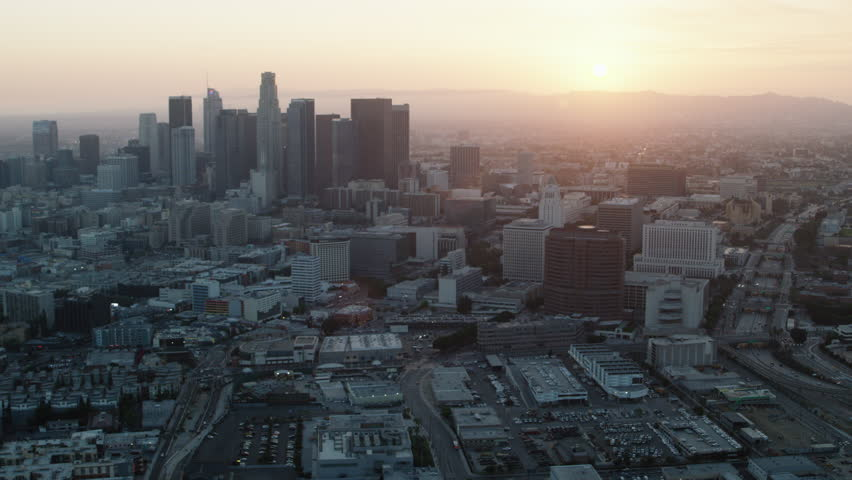Aerial view of urban city at sunset. Shot of skyscrapers and buildings in downtown Los Angeles. Shot with a RED camera. 4k footage.