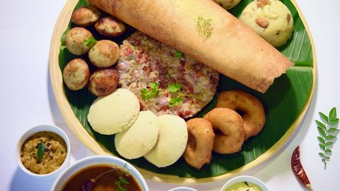 Footage of south indian food like masala dosa, uttapam, idli/idly,  wada/vada, sambar, appam, semolina halwa, upma served over banana leaf with  colourful chutneys, selective focus