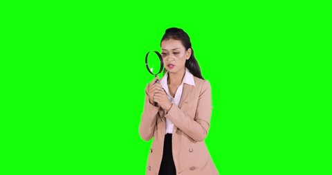 Young business woman looking through magnifying glass in the studio. Shot in 4k resolution with green screen background