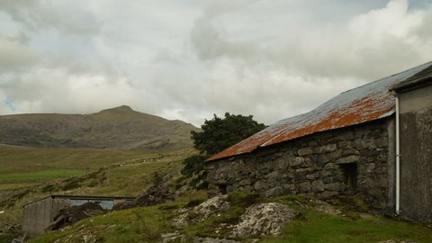 Clouds over an old barn in front of Mount Snowdon in Snowdonia National Park, Wales.
