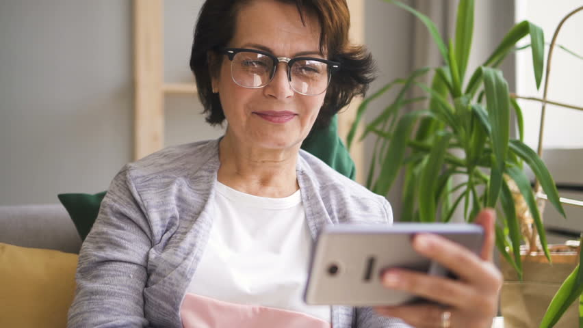 Mature woman in glasses, with brown hair having video call on her smartphone, smiling and waving hand sitting on sofa at home. Indoors. Portrait.