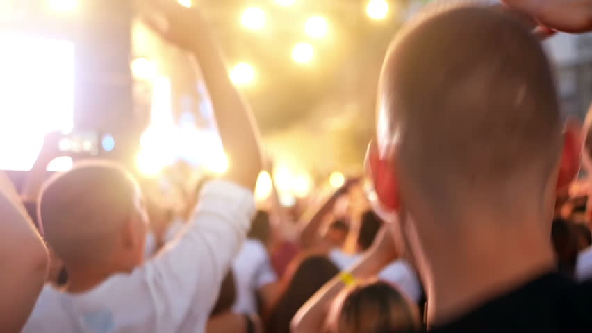Crowd partying at a rock concert. Silhouetted hands and flashing lights   Shutterstock HD Video #1014885811
