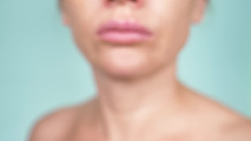 herpes on the female lips. 4k, close-up, blue background, blur, slow-motion