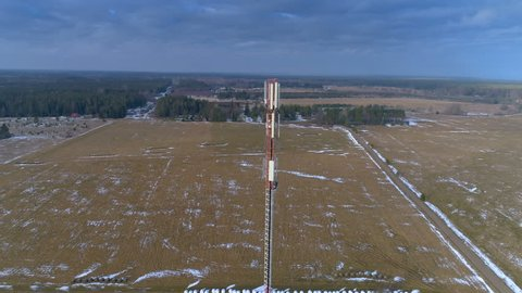 The aerial view of the GSM 4G 5G glas micro fibre communications tower in the field with the white snow on ground field