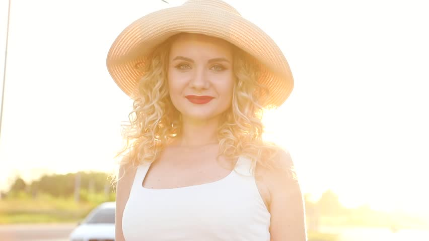 Close up view of Pretty Young Woman Walking like a Model. Looking at the Camera. Enjoying her Life. Wearing Stylish Straw Hat. Having Elegant Make up. Girl with Curly Blond Hair. Red Lips. Sunset.