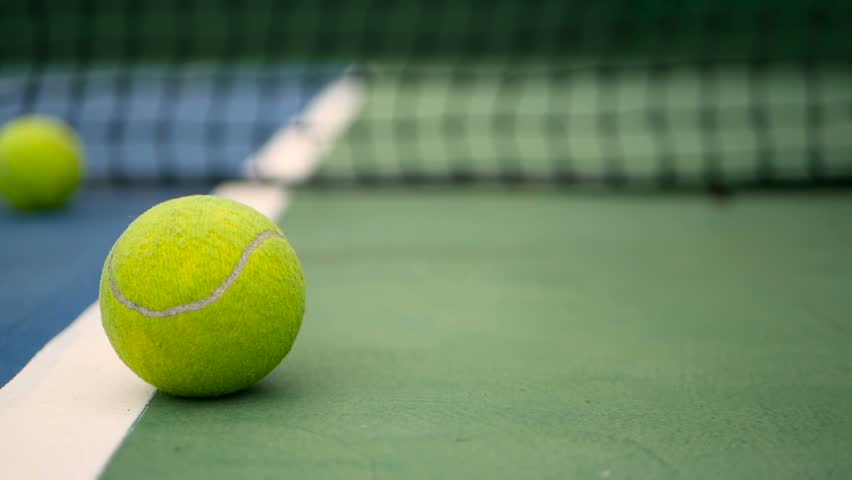 Close up of tennis equipment on the court. Sport, recreation concept. Yellow tennis balls in motion on a clay green blue court next to the white line with copy space, soft focus and net in background. | Shutterstock HD Video #1014932521
