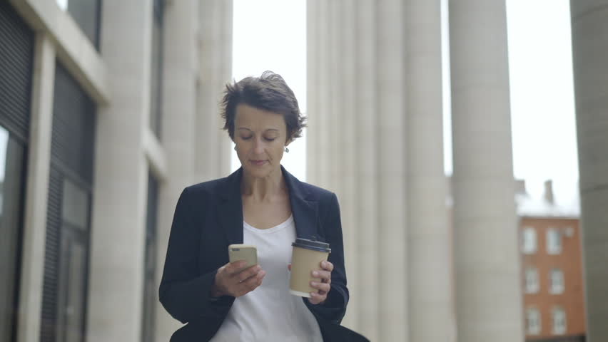 Medium dolly shot of elegant middle aged businesswoman with short hair walking down street with cell phone and takeaway coffee cup in her hands and looking around thoughtfully | Shutterstock HD Video #1014957211