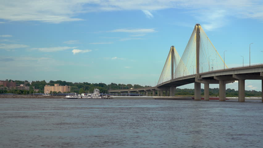 A towboat with barges is passing under the Clark bridge on the Mississippi River at Alton.