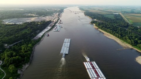 Barges passing rock quarry on the Mississippi River in 4k.