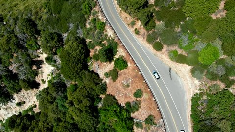 Drone Shot Looking Down on a Group of Cars Traveling Along the Side of a Mountain near Lake Arrowhead, California and Panning Up