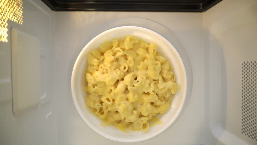 Making microwave meal. Macaroni and cheese in bowl microwaving top view.