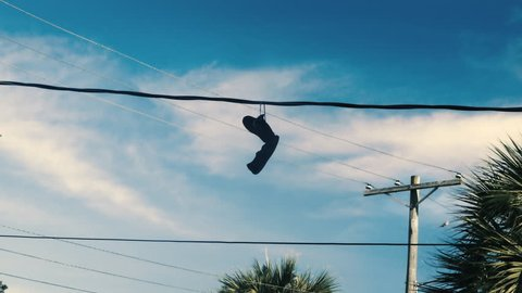 Sneakers hanging from power lines, urban street culture