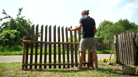 Men's hands clog the nail. Hammer in hand. Handsome guy makes a fence. A beautiful model hammers a nail with a hammer.An employee makes a fence.