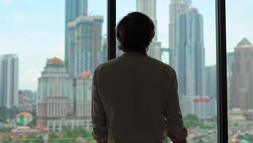 silhouette of a successful rich man opening the curtains of a window overlooking the city center with skyscrapers