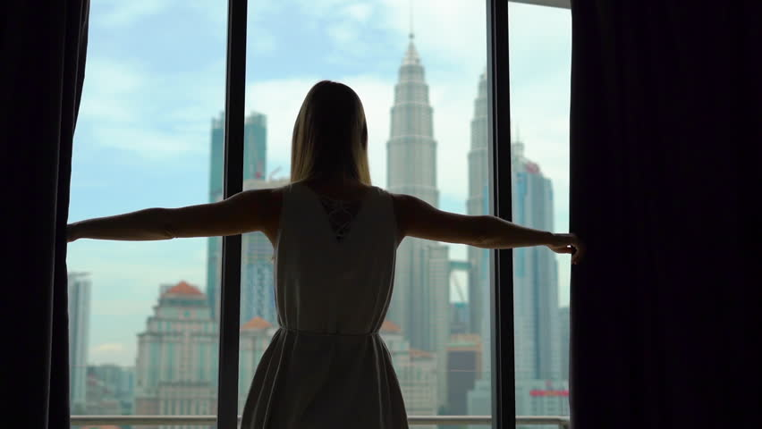 Superslowmotion shot of a silhouette of a successful rich woman opening the curtains of a window overlooking the city center with skyscrapers.