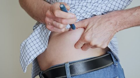 A man with diabetes making injection with insulin pen on belly