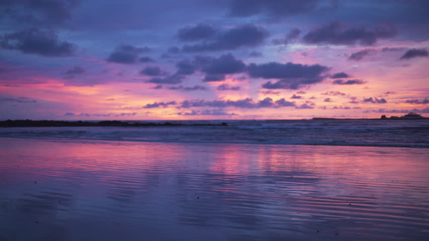 Out of focus background plate of remarkable purple and blue sunset on the beach in Costa Rica for compositing or keying. Blurred or defocused shot of ocean sun set for green screen composite. 4k
