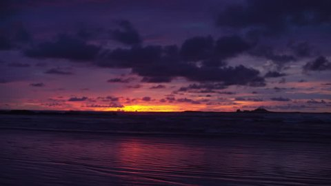 Out of focus background plate of deep purple and orange sunset on the beach in Costa Rica for compositing or keying. Blurred or defocused shot of ocean sun set for green screen composite. 4k