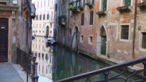Typical Venetian homes with arched doorways and windowsills with plants on a narrow canal. View from behind iron rail of old Italian structure with weathered stonework. 4k