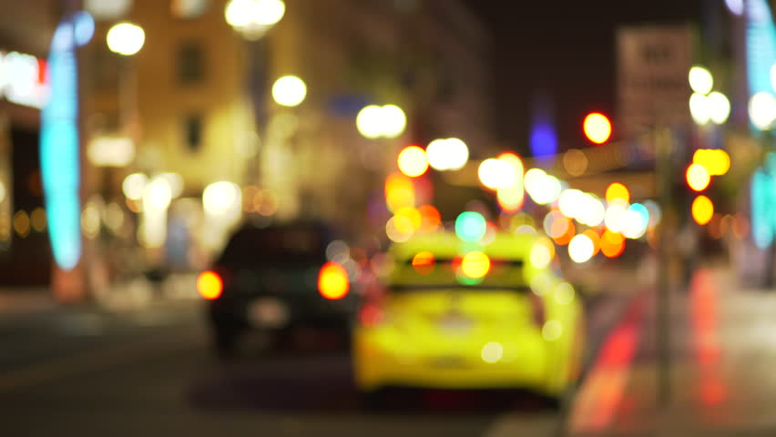 Out of focus background plate of taxi cab line parked on city street downtown at night. Defocused Video backdrop of urban area with bokeh lights for green screen compositing. 4k
