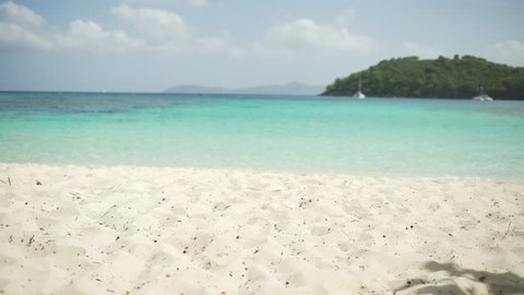 Sand-level shot of the Caribbean tide coming in on the island of St John's for green screen or chroma key. Out of focus or defocused background plate for compositing or keying.