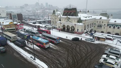 Aerial Forward Railway Station building Vladivostok Russia Train historical monument decor symbol Trans-Siberian Railway Port horn Cityscape Tourist attraction landmark Winter snow overcast Blizzard