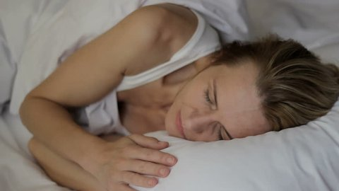 Sleepyhead female wants not to get up from comfortable bed, yawning slumberous