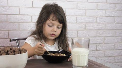 Children have breakfast. Little girls eat chocolate cornflakes.